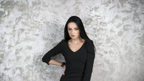 Портрет красивой молодой женщины в черном платье на абстрактной серой предпосылке Стоковое Фото