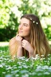 Портрет красивой молодой женщины лежа на зеленой траве outdoors Стоковое Фото