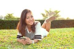Портрет красивой молодой женщины лежа на поле зеленой травы и Стоковое фото RF