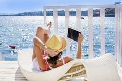 Портрет красивой молодой женщины лежа на sunbed с таблеткой в руке Стоковые Фотографии RF