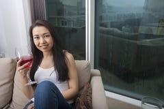 Портрет красивой молодой женщины держа стекло красного вина в живущей комнате Стоковая Фотография