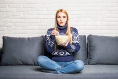Портрет красивой молодой женщины есть попкорн пока смотрящ кино в живущей комнате Стоковое фото RF
