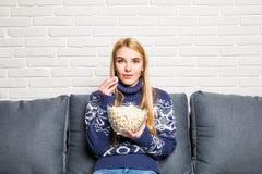 Портрет красивой молодой женщины есть попкорн пока смотрящ кино в живущей комнате Стоковое Фото