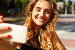 Портрет красивой молодой женщины делая selfie на умном телефоне Стоковые Изображения