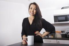 Портрет красивой молодой женщины имея кофе в кухне Стоковые Изображения RF