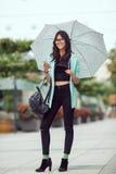 Портрет красивой молодой женщины используя ее мобильный телефон в улице Стоковые Изображения