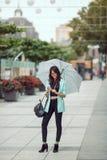 Портрет красивой молодой женщины используя ее мобильный телефон в улице Стоковая Фотография RF
