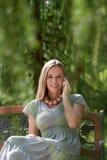 Портрет красивой молодой женщины используя мобильный телефон на скамейке в парке Стоковое Изображение