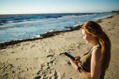 Портрет красивой молодой женщины касаясь экрану телефона на предпосылке моря Девушка повернута к заходу солнца Стоковое Изображение RF