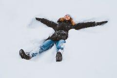 Портрет красивой молодой женщины кладя вниз на замороженное озеро снега двигая ее оружия и ноги вверх и вниз создавать ангела f с Стоковые Изображения RF