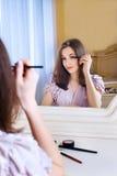 Портрет красивой молодой женщины кладя на состав Стоковая Фотография