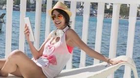 Портрет красивой молодой женщины кладя на sunbed с таблеткой в руке Стоковые Изображения RF