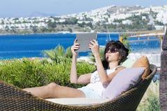 Портрет красивой молодой женщины кладя на sunbed с таблеткой в руке Стоковое Изображение