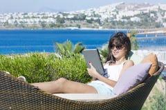 Портрет красивой молодой женщины кладя на sunbed с таблеткой в руке Стоковое Фото