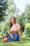 Портрет красивой молодой женщины ослабляя на траве в парке Стоковое Фото