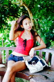 Портрет красивой молодой женщины при сумка сидя на стенде, летние каникулы Стоковые Фотографии RF