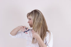 Портрет красивой молодой женщины расчесывая ее волосы и усмехаться Стоковое Фото