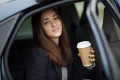 Портрет красивой молодой женщины сидя в автомобиле с кофе Стоковая Фотография