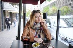 Портрет красивой молодой женщины сидя в кафе улицы Стоковые Фотографии RF