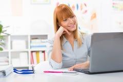 Портрет красивой молодой женщины сидя ее стол и смотря компьтер-книжку Стоковые Фото