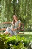Портрет красивой молодой женщины сидя на стенде в парке Стоковые Фото