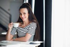 Портрет красивой молодой женщины сидя на таблице с чашкой кофе в руке смотря камеру усмехаясь пока на Стоковое Изображение RF