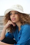 Портрет красивой молодой женщины сидя outdoors с шляпой Стоковые Изображения
