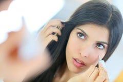 Портрет красивой молодой женщины смотря зеркало Стоковые Изображения