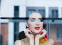Портрет красивой молодой женщины стоя около окна и l Стоковые Изображения RF