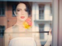 Портрет красивой молодой женщины стоя около окна и l Стоковая Фотография