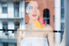 Портрет красивой молодой женщины стоя около окна и l Стоковое Изображение RF