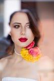 Портрет красивой молодой женщины стоя около окна и l Стоковые Фото