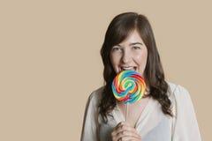 Портрет красивой молодой женщины с леденцом на палочке над покрашенной предпосылкой Стоковая Фотография