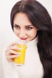 Портрет красивой молодой женщины с стеклом сока и апельсина, на белой предпосылке Стоковая Фотография