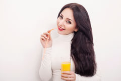 Портрет красивой молодой женщины с стеклом сока и апельсина, на белой предпосылке Стоковое фото RF