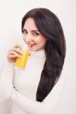 Портрет красивой молодой женщины с стеклом сока и апельсина, на белой предпосылке Стоковая Фотография RF