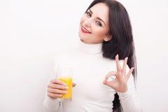 Портрет красивой молодой женщины с стеклом сока и апельсина, на белой предпосылке Стоковое Изображение RF