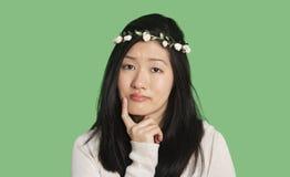 Портрет красивой молодой женщины думая с рукой на ее подбородке над зеленой предпосылкой Стоковое фото RF