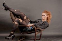 Портрет красивой молодой красной курчавой девушки с ярким составом в сорванном колготки в кресле Стоковое фото RF