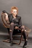 Портрет красивой молодой красной курчавой девушки с ярким составом в сорванном колготки в кресле Стоковое Изображение