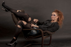 Портрет красивой молодой красной курчавой девушки с ярким составом в сорванном колготки в кресле Стоковые Фото