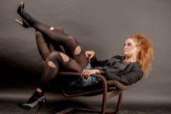 Портрет красивой молодой красной курчавой девушки с ярким составом в сорванном колготки в кресле Стоковое Изображение RF