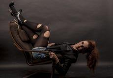 Портрет красивой молодой красной курчавой девушки с ярким составом в сорванном колготки в кресле Стоковая Фотография