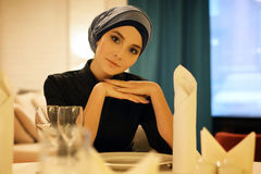 Портрет красивой мусульманской женщины сидя на таблице в ресторане Стоковые Фото