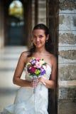 Портрет красивой невесты в белом платье, которое положилось на каменном столбце стоковые изображения rf