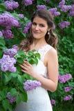 Портрет красивой невесты представляя около зацветая дерева сирени Стоковая Фотография RF