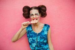 Портрет красивой нежной белокурой девушки с голубыми глазами в розовом платье с леденцом на палочке, закрывая один глаз, на светл Стоковая Фотография