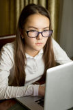 Портрет красивой предназначенной для подростков девушки в eyeglasses используя компьтер-книжку Стоковые Изображения RF