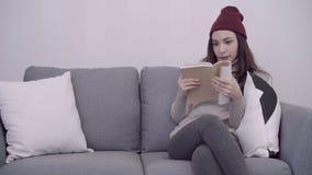 Портрет красивой привлекательной азиатской женщины читая книгу пока сидящ на софе когда ослабьте в живущей комнате дома видеоматериал