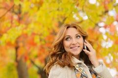 Портрет красивой привлекательной молодой женщины говоря на phon Стоковое Изображение